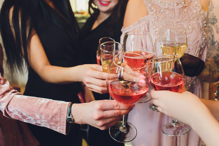 Champagne glasses in hands of people at party.