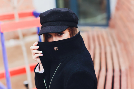 portrait of fashionable woman walking in city in coat wearing black cap. Stock Photo