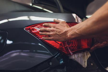 mechanic matching automobile headlight lamp to damaged car at repair service station 版權商用圖片