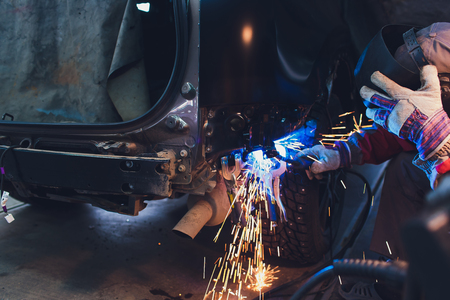 professional repairman worker in automotive industry welding metal body car with sparks Banque d'images