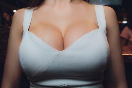 Decolleté, vrouwelijke borst. Halslijn witte jurk en bontkraag. Stockfoto