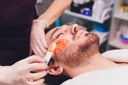 Hair removal. Mans face sugaring epilations beard trimming, yellow color, in cosmetology on the couch. Archivio Fotografico