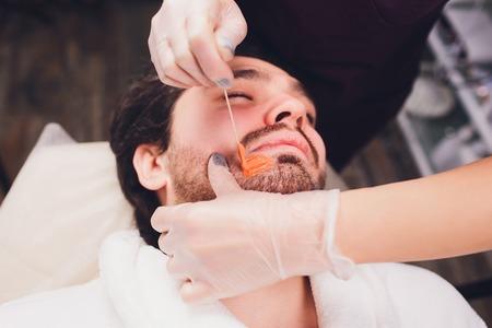 Rimozione peli. Mans faccia zuccheraggio epilazioni barba taglio, colore giallo, in cosmetologia sul divano.