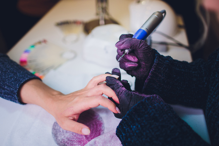 Hands in gloves cares about mans hand nails. Manicure beauty salon. Stok Fotoğraf