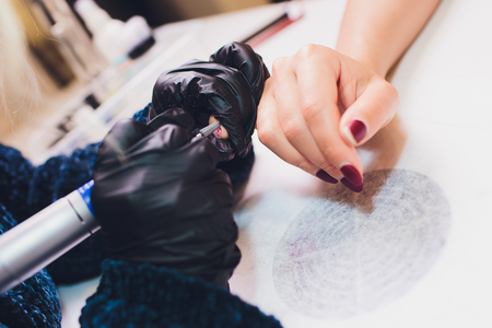 Hands in gloves cares about mans hand nails. Manicure beauty salon. 写真素材