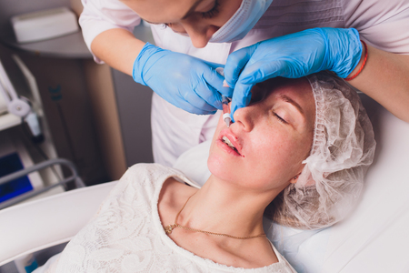 The doctor cosmetologist makes Lip augmentation procedure of a beautiful woman in a beauty salon.Cosmetology skin care. Imagens