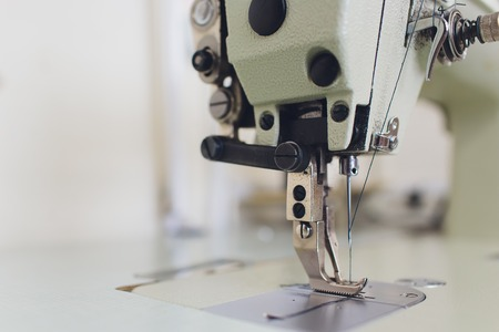 Professional sewing machine on the background of atelier studio. Workplace of tailor - sewing machine, rolls of thread, fabric, scissors. Sewing business concept.