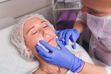 The doctor cosmetologist makes facial injections procedure for tightening and smoothing wrinkles on the face skin of a beautiful, young woman in a beauty salon. Cosmetology skin care.