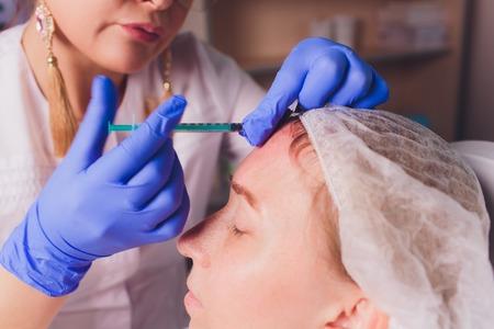 의사 미용사는 미용실에서 아름답고 젊은 여성의 얼굴 피부에 주름을 조이고 부드럽게 하기 위한 안면 주사 절차를 만듭니다. 미용 피부 관리. 스톡 콘텐츠