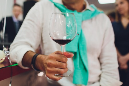 man hand holding glass of wine in the room. party, drinks, holidays, luxury and celebration concept.
