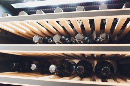 Almacenamiento de botellas de vino en la nevera. Tarjeta alcohólica en restaurante. Enfriamiento y conservación del vino.