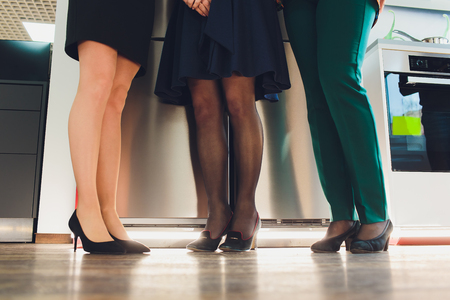 Legs of businesspeople. Woman wearing skirt, stockings and high heels, man wearing dark trousers and shoes.