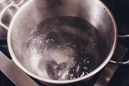 khinkali or dumplings are boiled in boiled water on the stove in a saucepan through steam. Cooking. black color. Stock Photo
