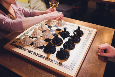 concept of Georgian cuisine. black and white khinkali stand on a chessboard. female hand takes khinkali. khinkali with barinas, veal and cheese.