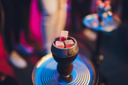 Shisha hookah with red hot coals. Sparks from breathe. Modern hookah for relax and shisha smoke.