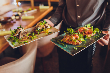 Two meat plate with salad leaves and summer salad in waiters hand. Stock Photo