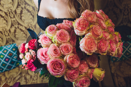 hand of beautiful young woman in black dress holding large bouquet of pink roses.
