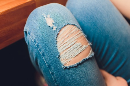 Woman in torn jeans blue texture fashion 스톡 콘텐츠