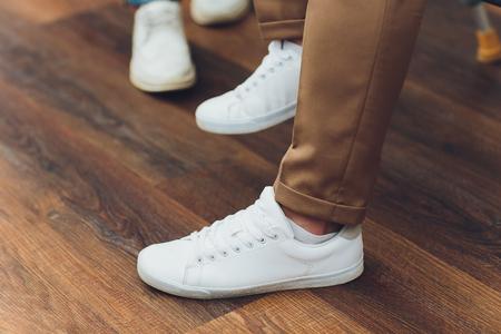White sneakers,lower half, legs, on wooden boards. Archivio Fotografico