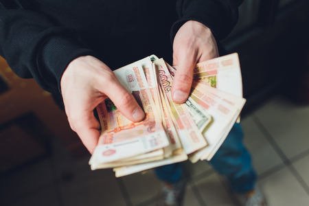 A man holds rubles and dollars in his hand, a businessman holds money in his hand.