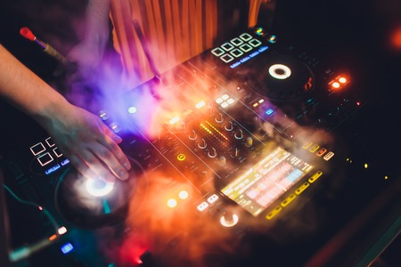Disc Jockey DJ Entertainment with EDM Dance Music Mixer CD Player in Night Club with Lighting and Smoke Effect in Holiday.