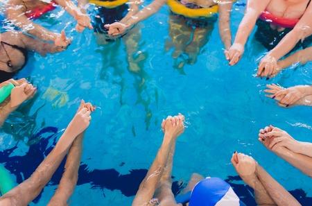 women trains in aqua aerobics, learn to swim. circle team hands Imagens