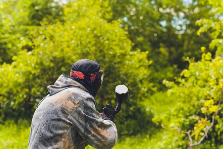 Paintball sport player in protective uniform and mask playing with gun outdoors.