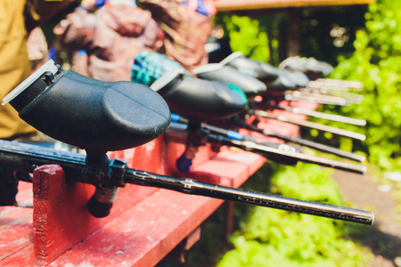 Paintball guns on a wooden table. play paintball