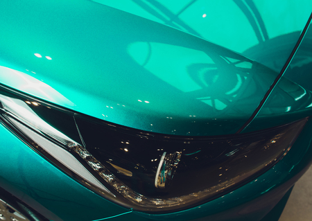 Close up of headlight detail of modern luxury car with projector lens for low and high beam. Front view of sport crossover vehicle head lamp. Concept of car detailing and light technology background