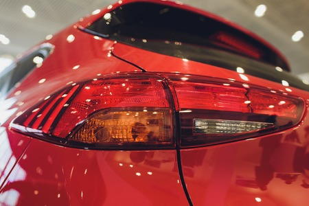 Close up of rear lights detail of modern luxury car with projector lens for low and high beam. Front view of sport crossover vehicle head lamp. Concept of car detailing and light technology background
