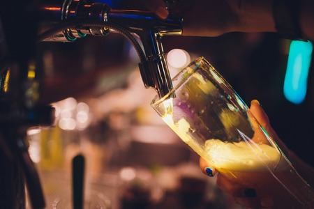 Hand of bartender pouring a large lager beer in tap Фото со стока - 124646427
