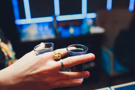 Hand holding a glass with vodka shot