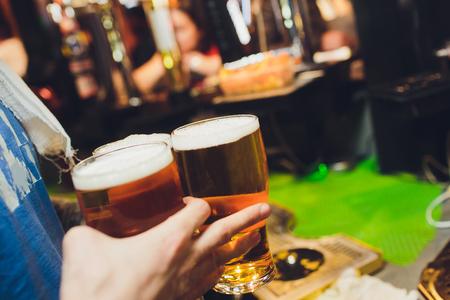 waiter holds glasses of beer in hands in a bar or pub. Beer glasses Banco de Imagens - 124645418