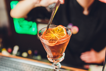 Glass of orange cocktail decorated with lemon at bar counter background