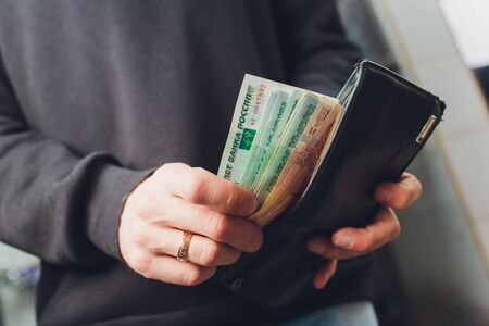 Hands take out russian rubles from wallet. Closeup on a mans hands as he is getting a banknote out of his wallet. Reklamní fotografie