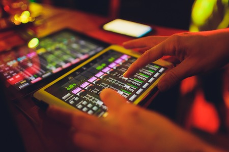 studio working with sound and light mixer console,hands of sound engineer working on recording studio mixer adjusting the volume of a sound mixer audio mixing console with digital mixer tablets