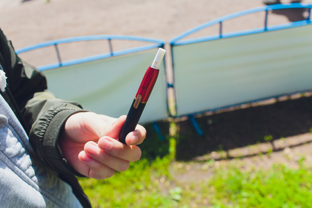 heat-not-burn tobacco product technology. Man holding e-cigarette in his hand before smoking