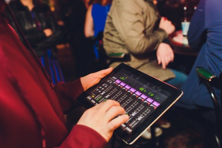 Event tuner controlling sound from tablet on the background of karaoke bar