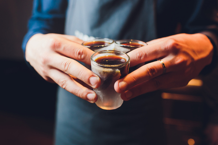 Male hands cheer with glasses of shot or liqueur. Friends drink shot or liqueur and cheers. Male hands cheer with alcohol on blurred bar background. Party and toast concept Banco de Imagens - 124644385