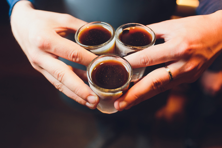 Male hands cheer with glasses of shot or liqueur. Friends drink shot or liqueur and cheers. Male hands cheer with alcohol on blurred bar background. Party and toast concept Stock Photo - 124644390