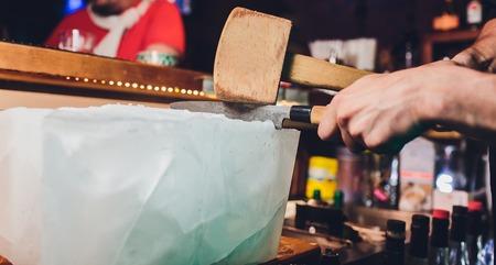 Barman snijdt een groot blok ijs om whiskycocktails te bereiden. Selectieve focus op het ijsblok. Gastvrijheid en fijn whiskyconcept Stockfoto
