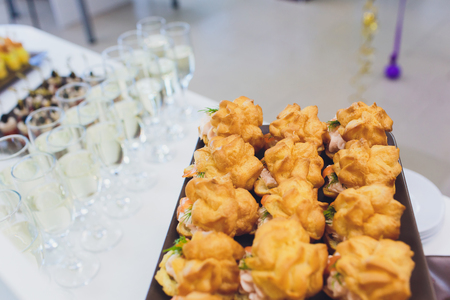 Beautifully decorated catering banquet table with burgers, profiteroles, salads and cold snacks. Variety of tasty delicious snacks on the table