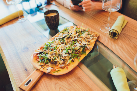 Italian fast food. Delicious hot pizza sliced and served on wooden platter with ingredients, close up view. Menu photo
