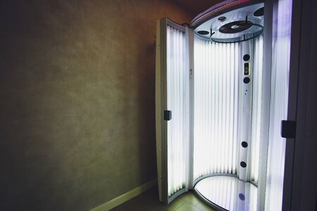 Vertical Tanning turbo Solarium Light Machine with glowing blue light ultraviolet lamps for tanning and skin care. Empty tanning Modern solarium, inside. Open Solarium door. Control panel on the side.
