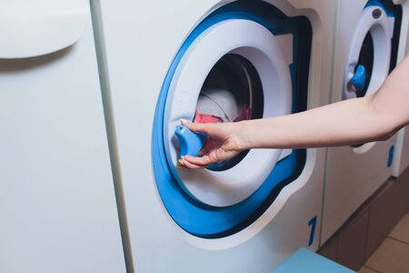 woman taking color clothes from washing machine.