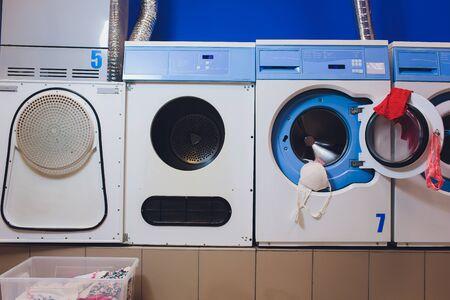 mujer tomando ropa de color de la lavadora.