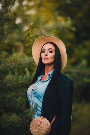 Tom Sawyer Mujer bonita en el sombrero de paja de pie delante de la valla. La mujer pintó una valla de madera. Foto de archivo