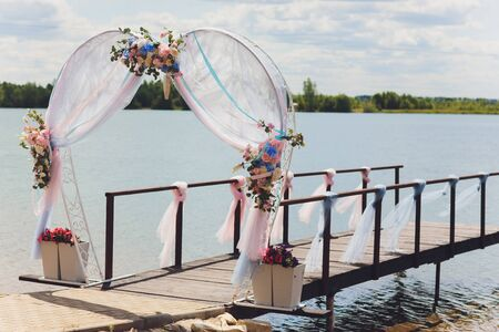 Part of the wedding arch decorated with fresh flowers is set on the sandy bank of the river. Wedding florist arranges workflow.