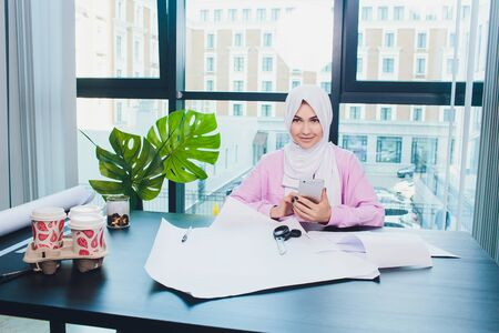 portrait of young attractive muslim woman fashion designer in her workshop smiling to camera.