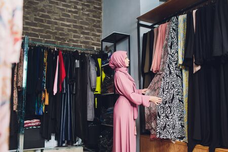 Arab woman in traditional Muslim clothes buys a new dress in an Oriental store Reklamní fotografie